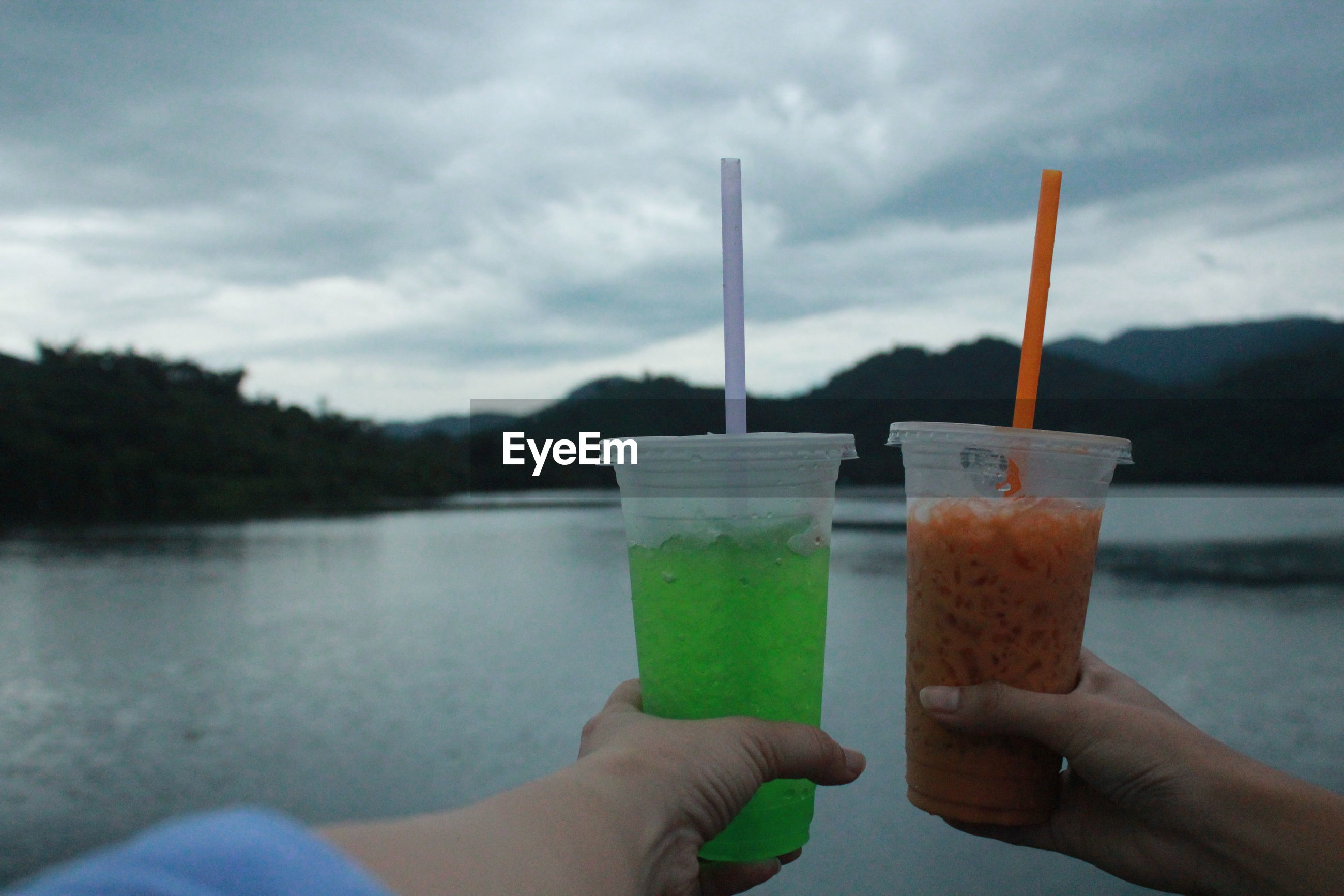 Cropped hands of people holding drinks at lake