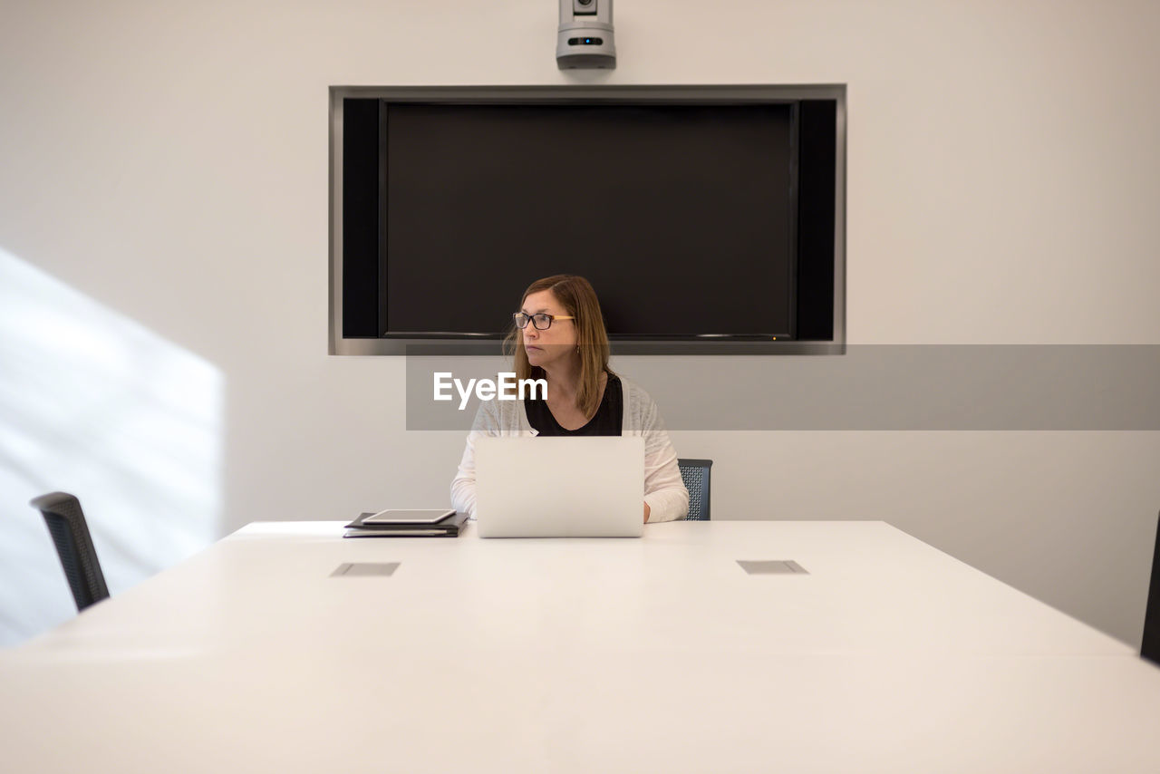 Businesswoman using laptop on table at office