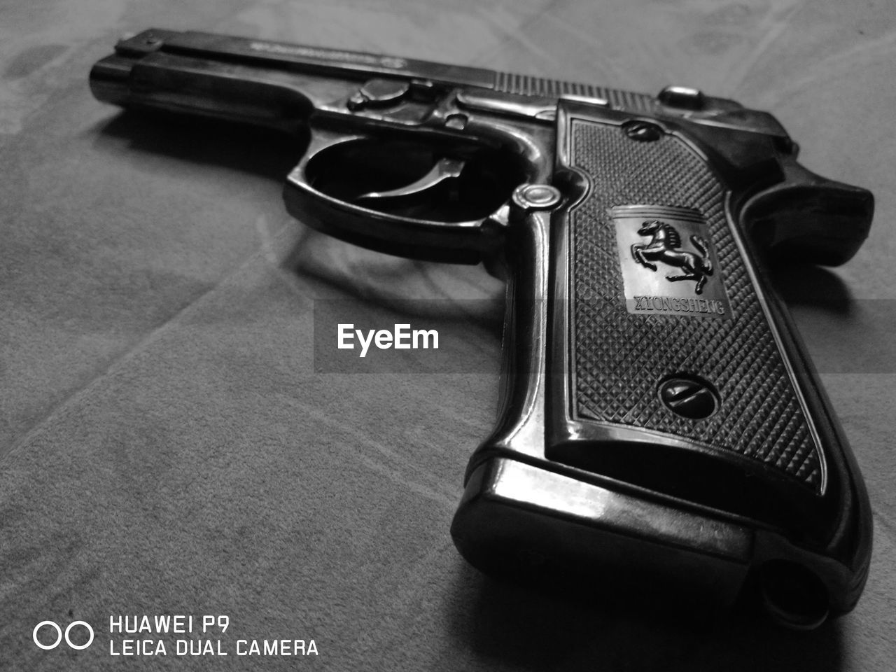 table, indoors, no people, close-up, handgun, weapon, day