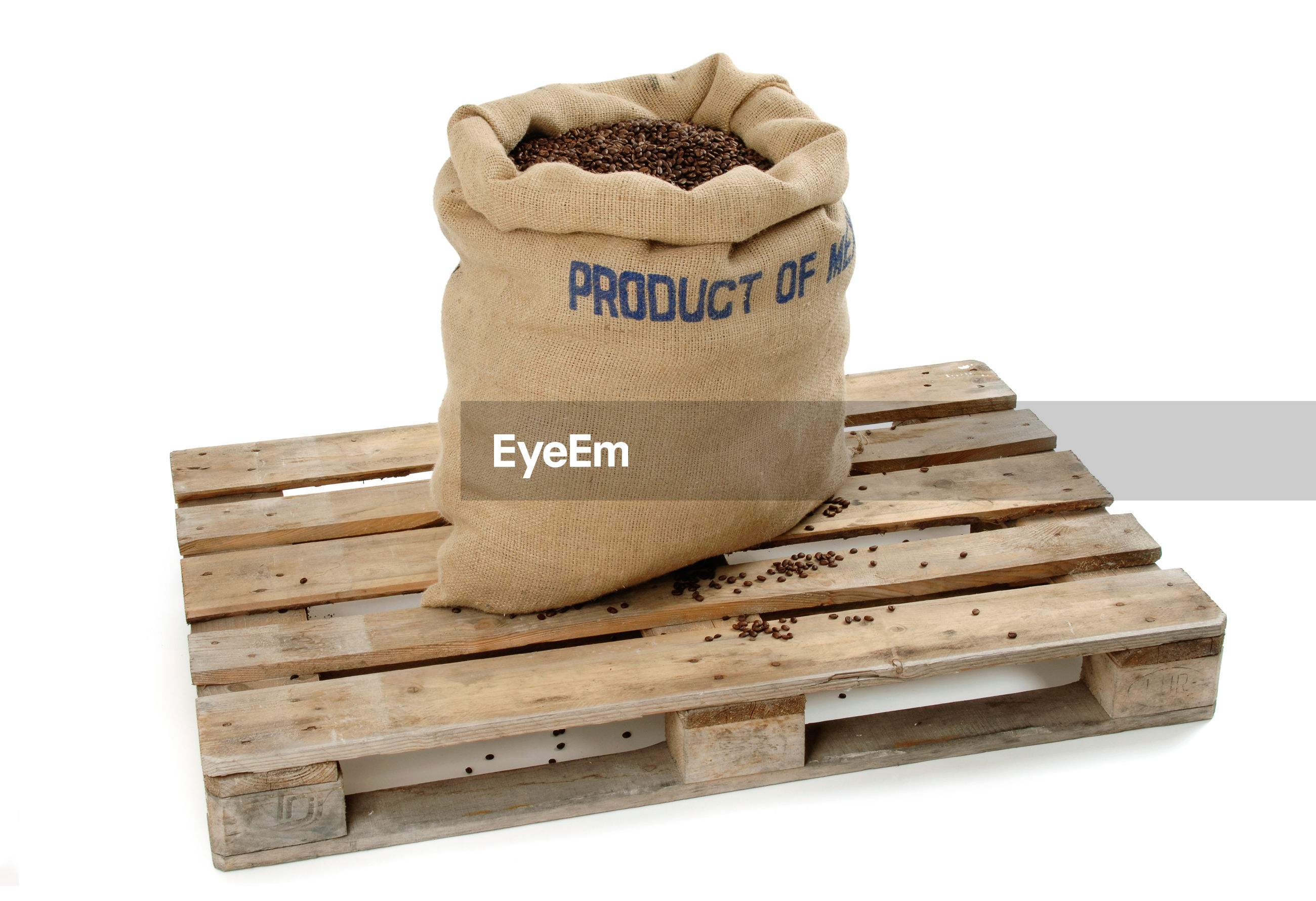 Coffee beans in sack on wood over white background