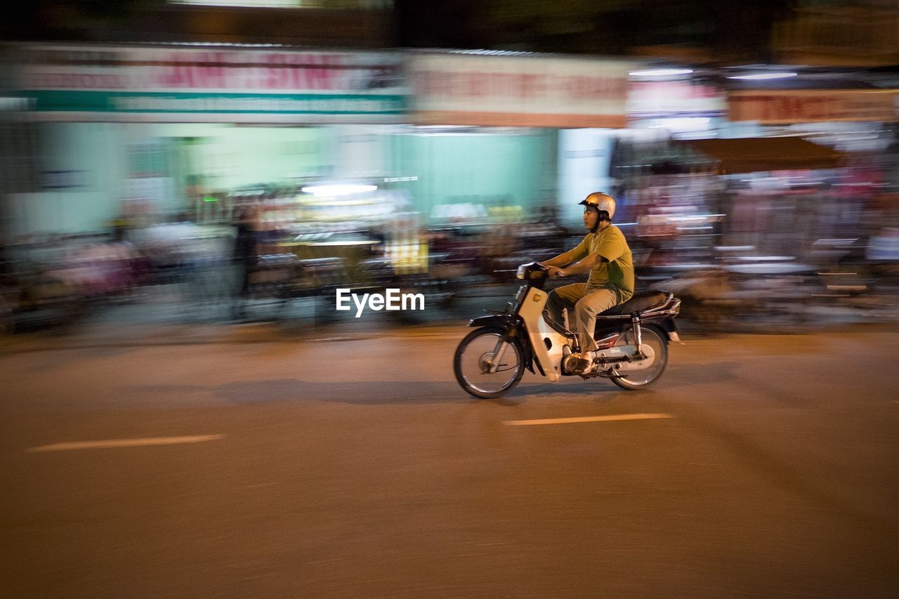 blurred motion, transportation, real people, motion, riding, speed, mode of transport, men, full length, street, one person, road, land vehicle, motorcycle, day, outdoors, city, adult, people