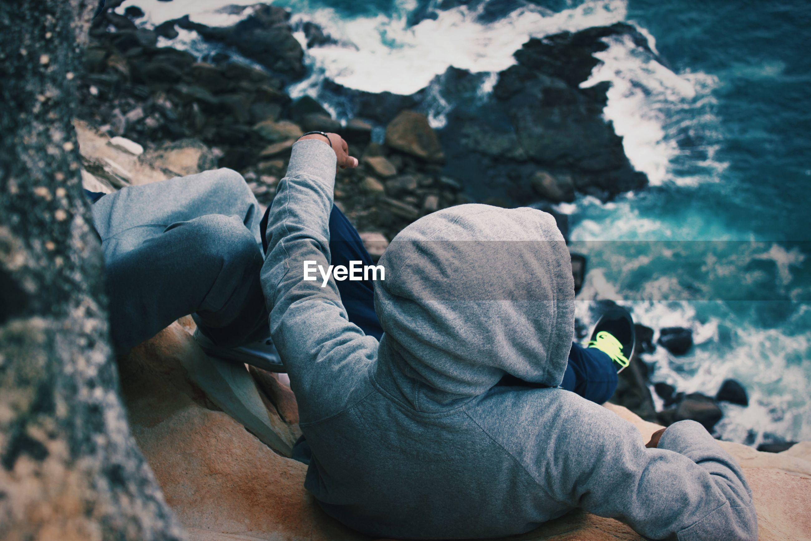 High angle view of man wearing hooded jacket sitting on sea shore