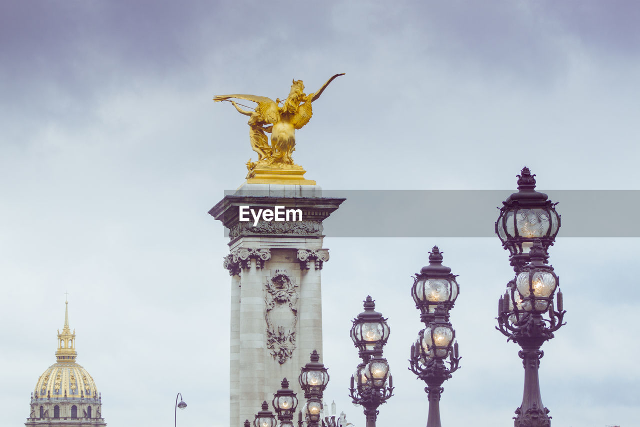 architecture, sky, built structure, art and craft, travel destinations, gold colored, cloud - sky, building exterior, no people, sculpture, travel, day, statue, representation, lighting equipment, tourism, nature, city, street light, human representation, outdoors, gilded, architectural column, angel