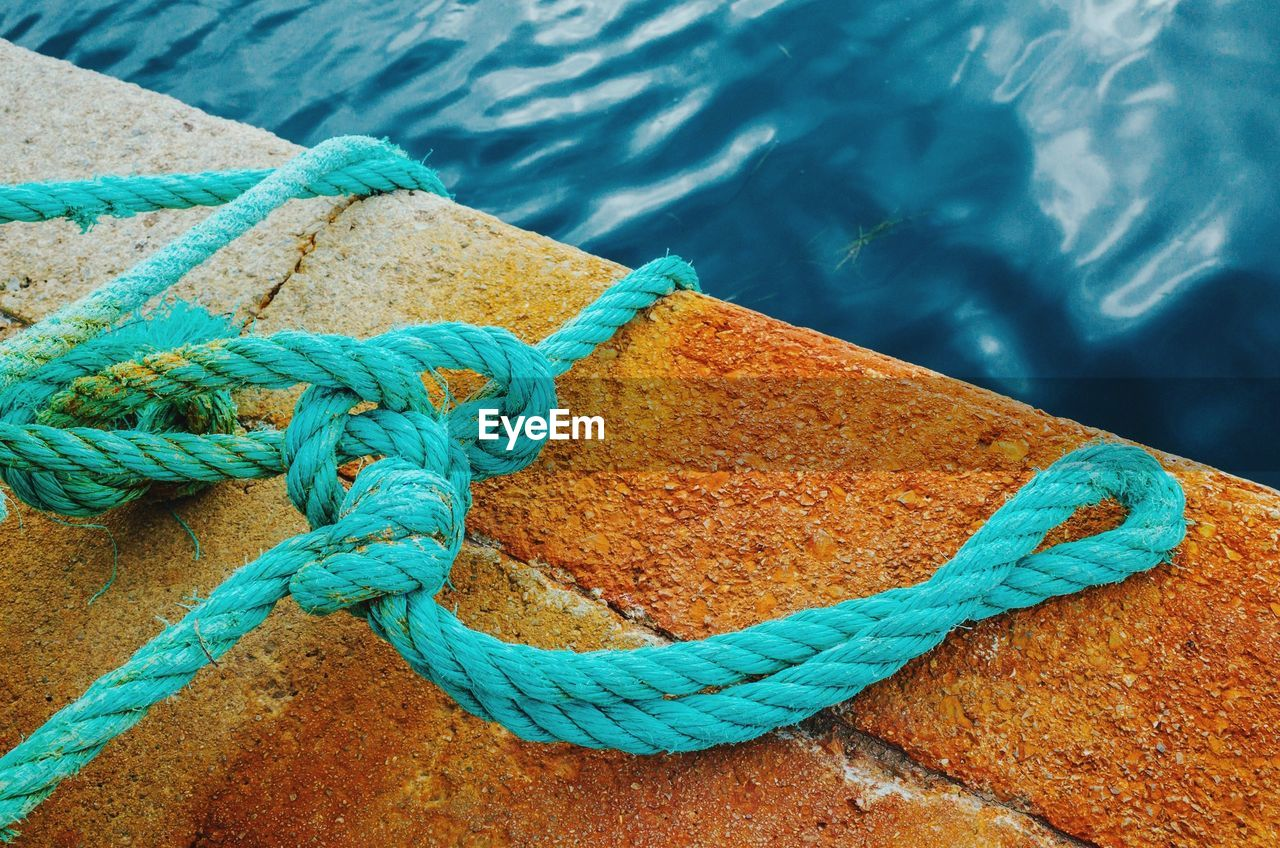 High Angle View Of Tangled Turquoise Rope On Pier
