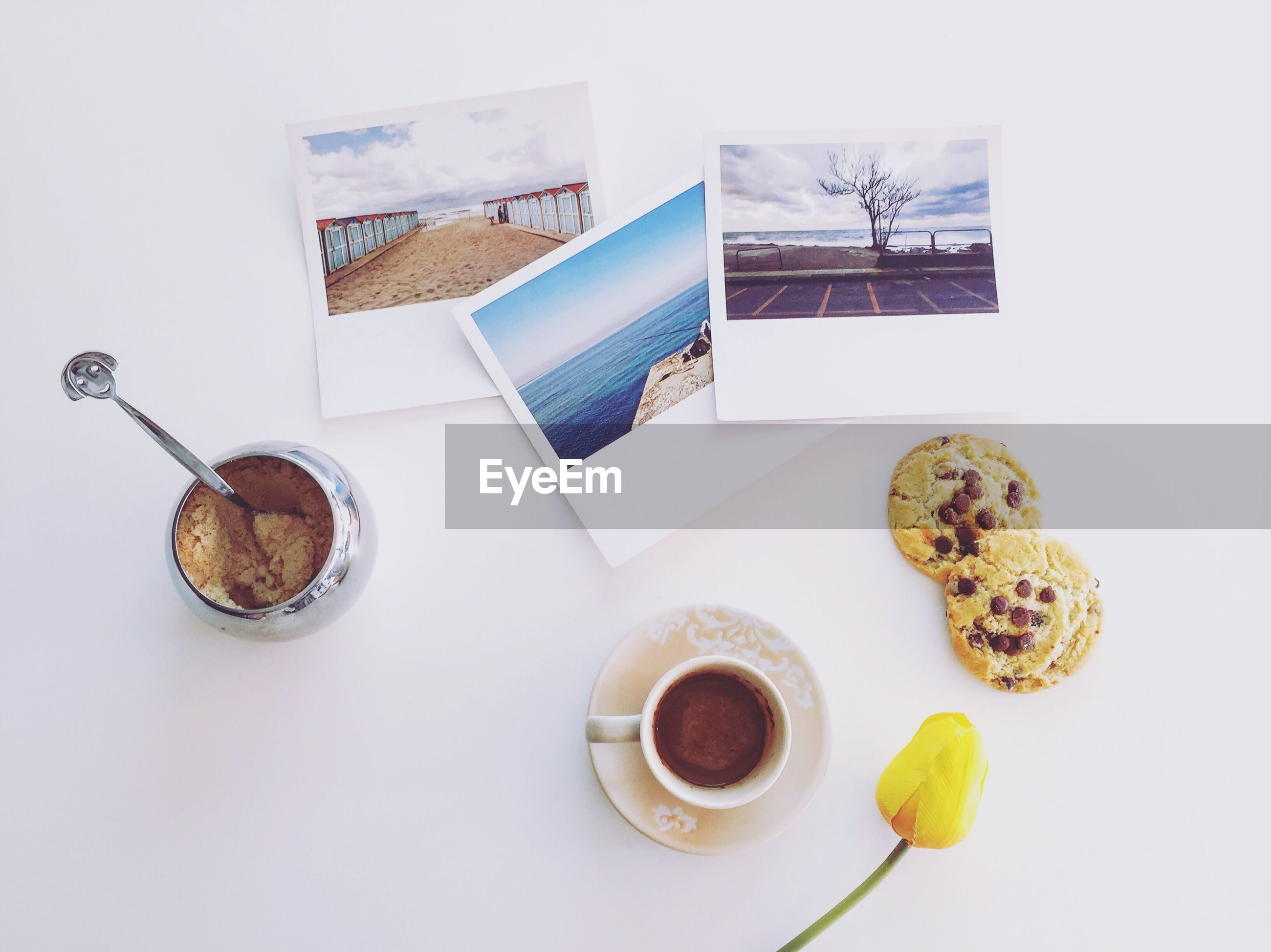 Directly above shot of coffee with flower bud by cookies and photographs on table