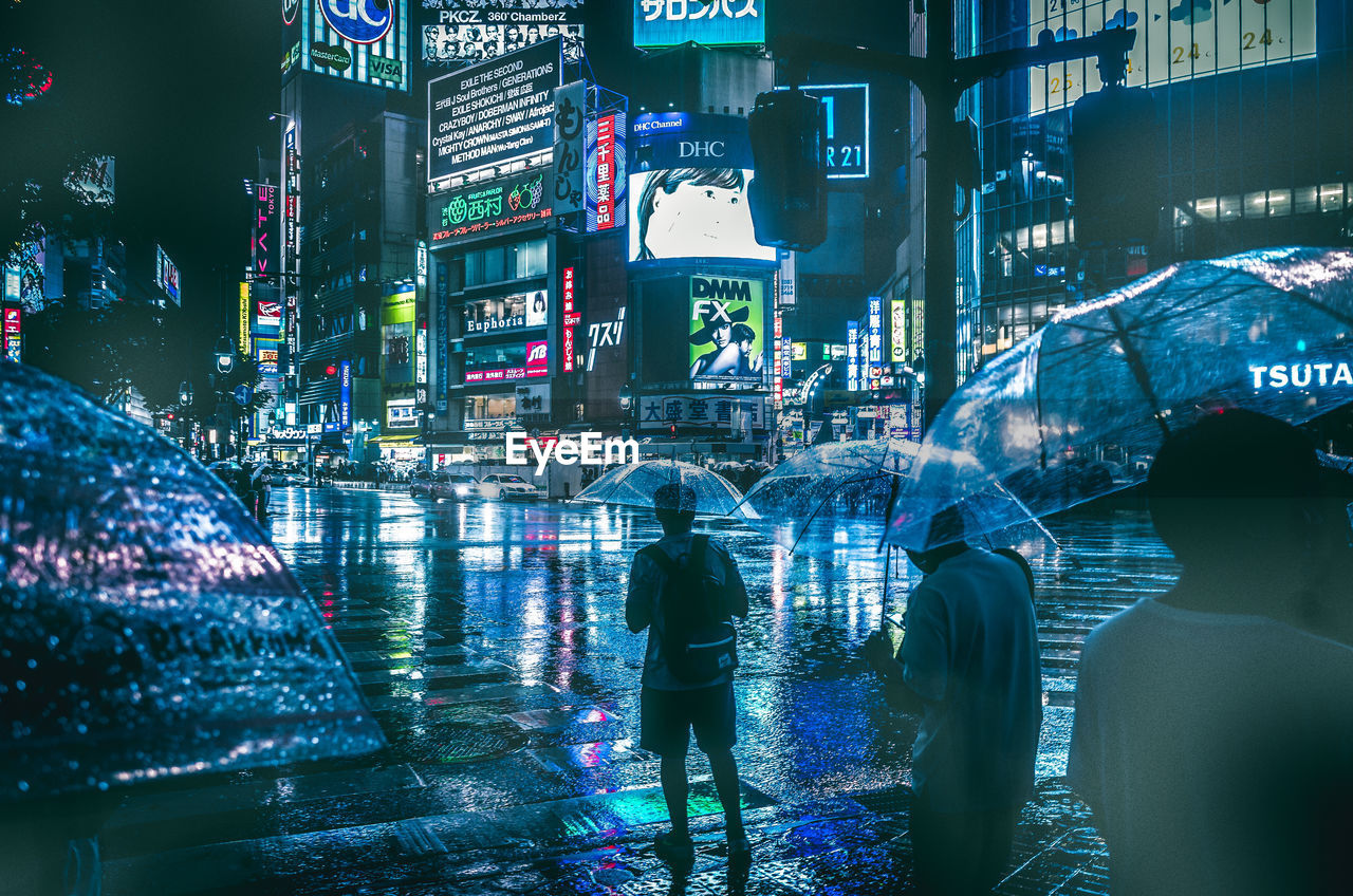 city, building exterior, architecture, built structure, illuminated, city life, group of people, night, real people, street, lifestyles, walking, women, rear view, umbrella, water, people, adult, city street, rain, outdoors, cityscape, rainy season, office building exterior
