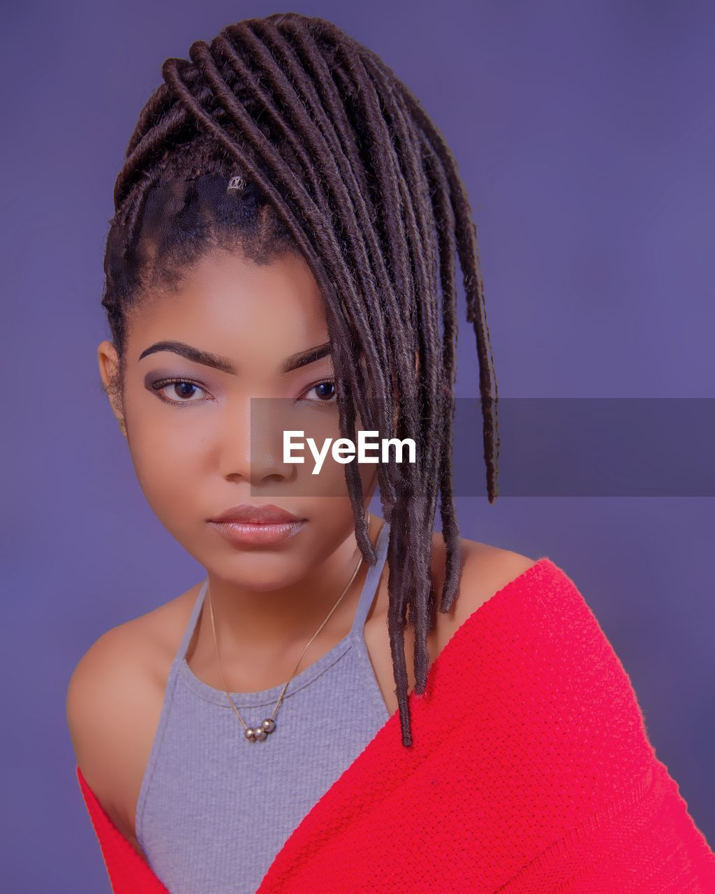 Portrait of beautiful young woman with dreadlocks against colored background