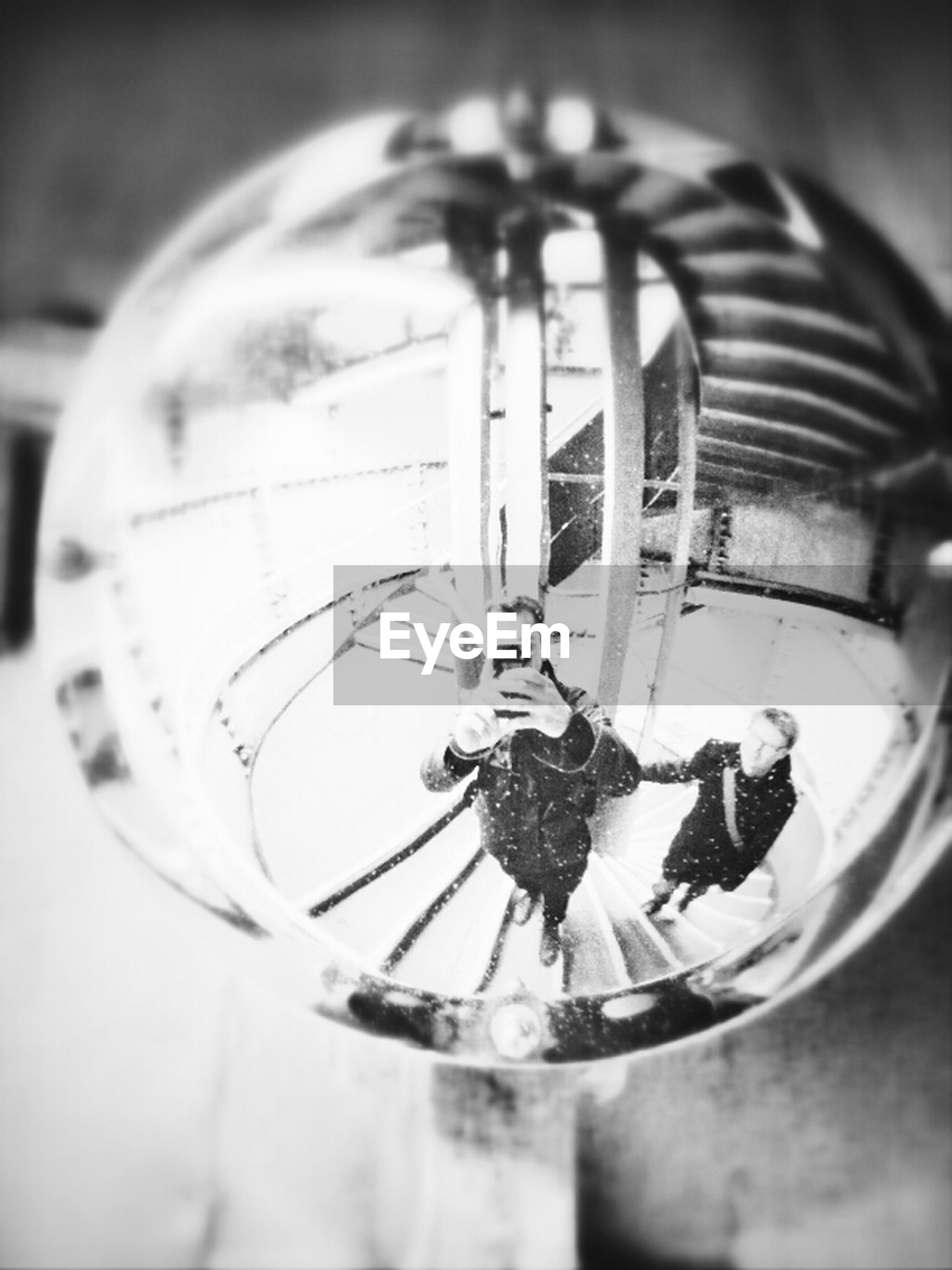 indoors, close-up, focus on foreground, glass - material, circle, low angle view, ceiling, no people, still life, lighting equipment, metal, reflection, home interior, arts culture and entertainment, hanging, transparent, table, selective focus, technology, shiny