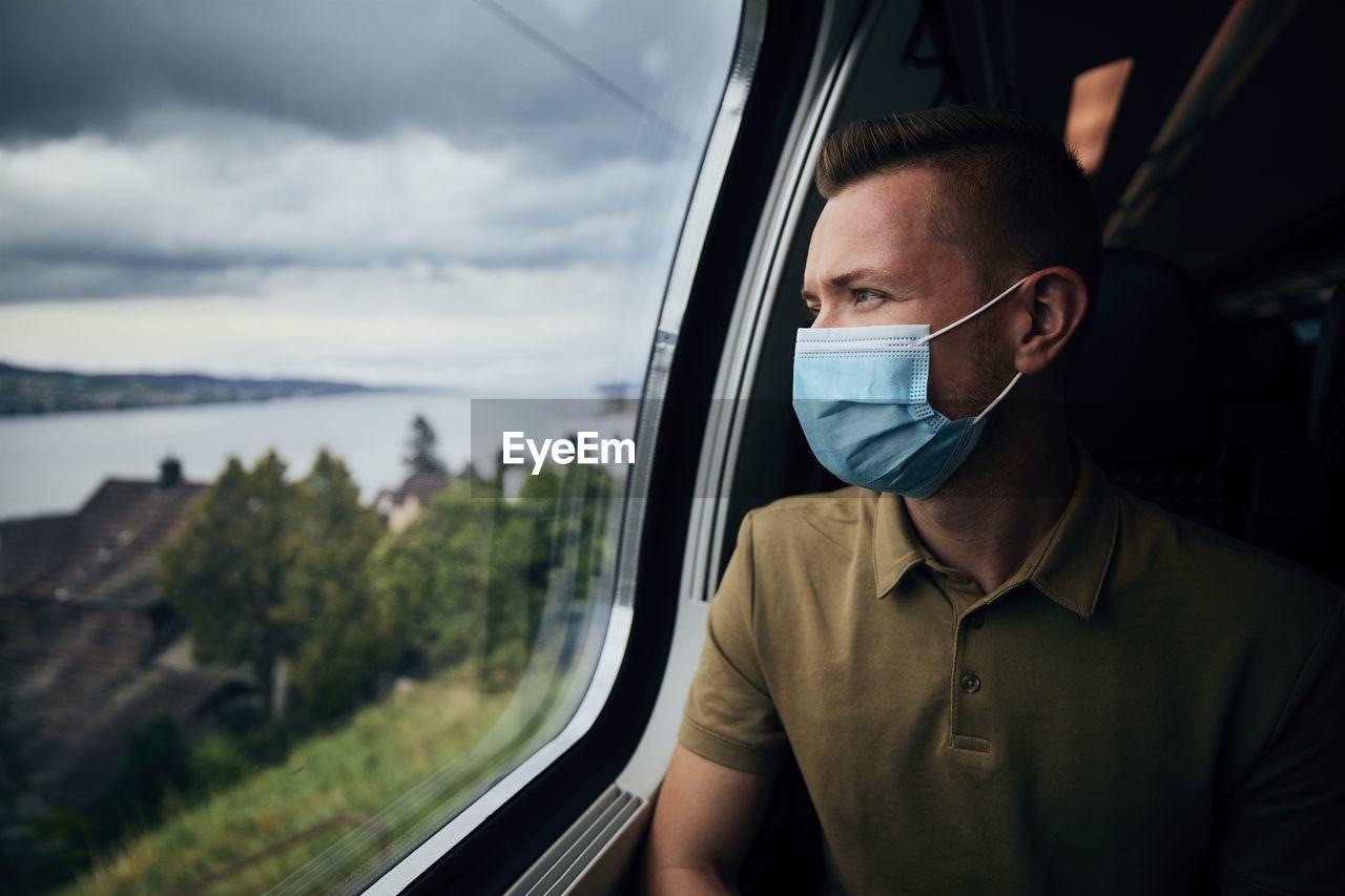 Man wearing mask looking through window in train