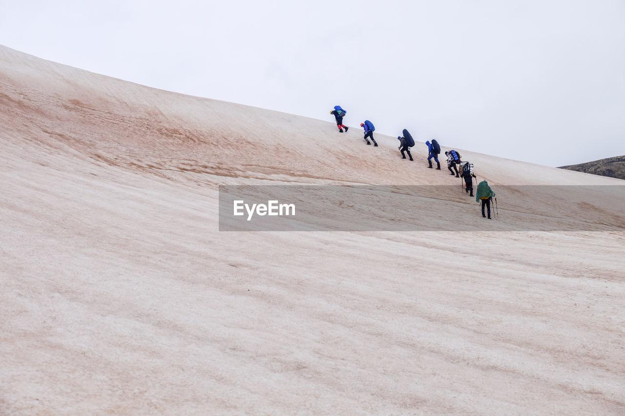 Hikers Climbing Sand Dunes In Desert