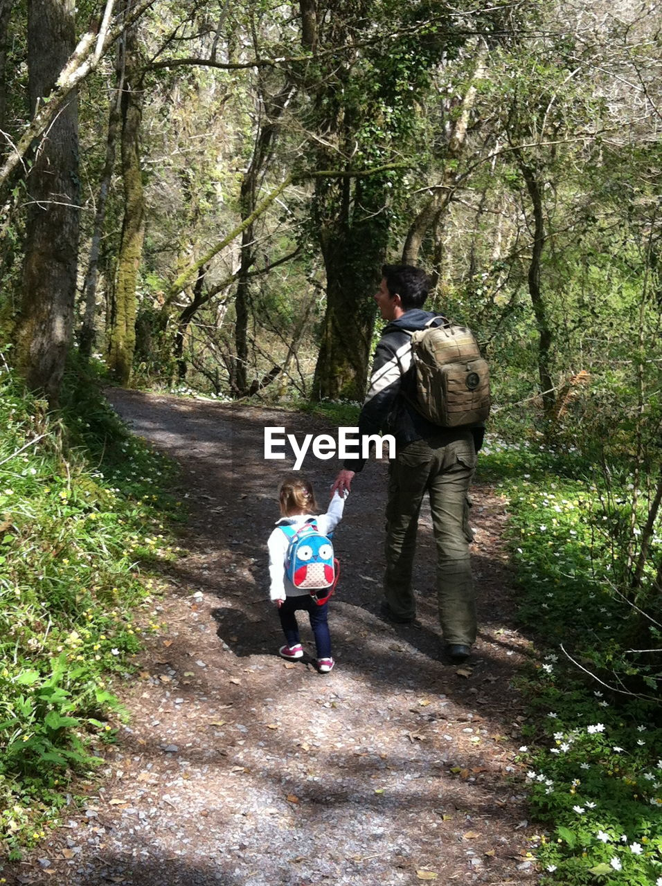 Full length rear view of father and daughter walking in forest with backpack