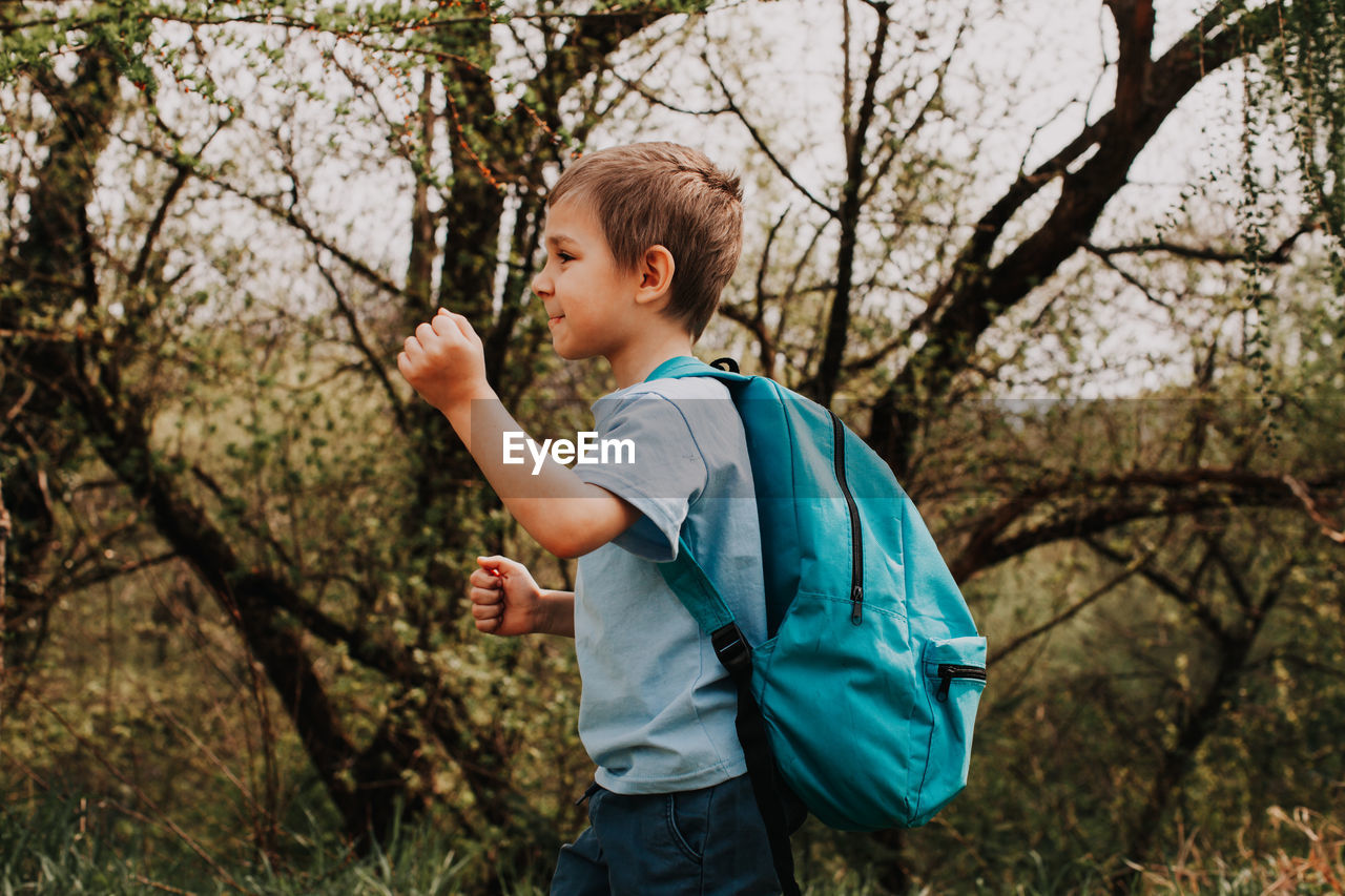 Side view of boy standing by tree