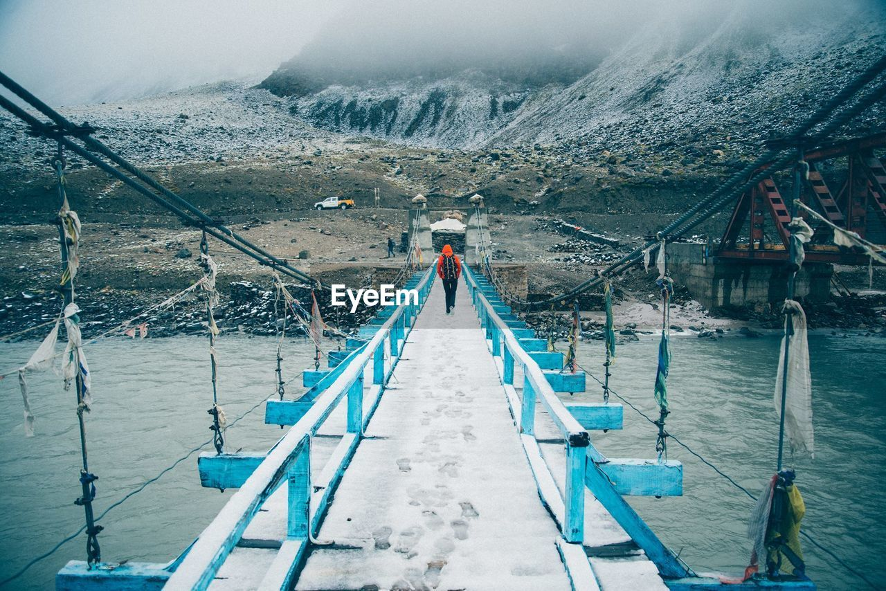 Rear View Of Man Walking Snowcapped Footbridge Over River During Winter