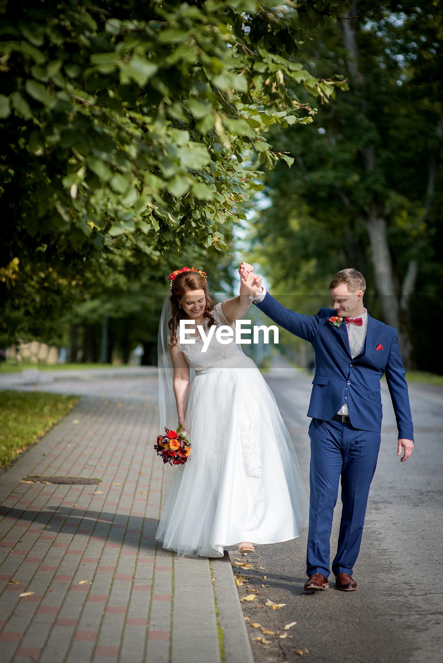 Bride and groom walking at park