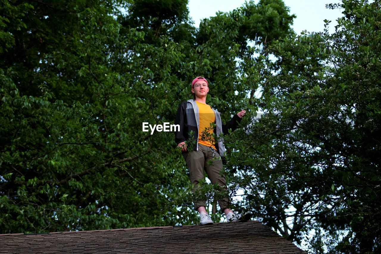 Low Angle View Of Young Man Standing On Rooftop Against Trees