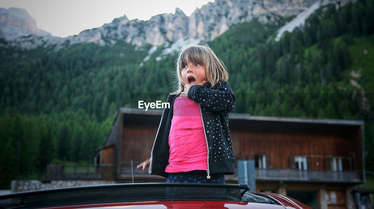 Shocked girl standing in car against mountains