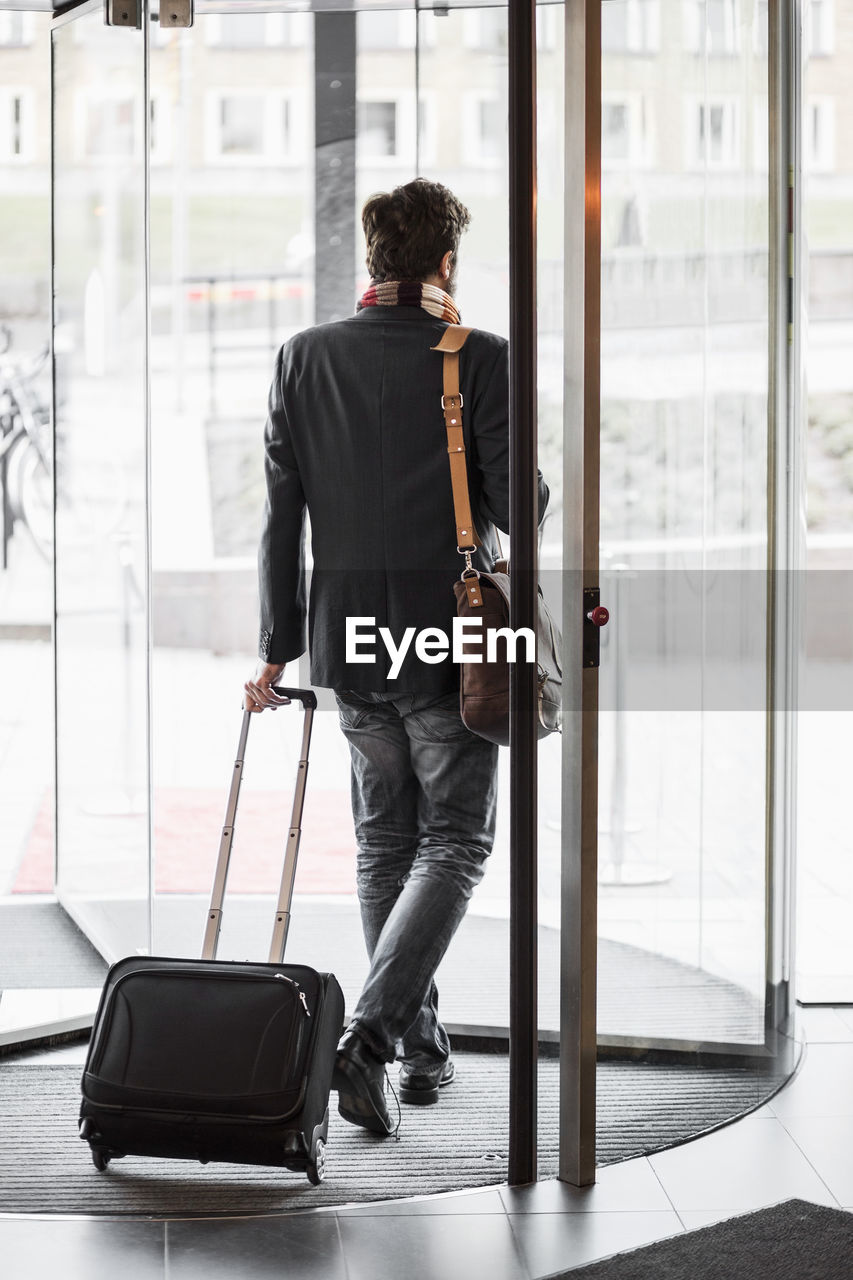 one person, full length, luggage, travel, businessman, business person, men, looking, glass - material, business, walking, suitcase, day, window, well-dressed, males, indoors, transportation, holding, leaving