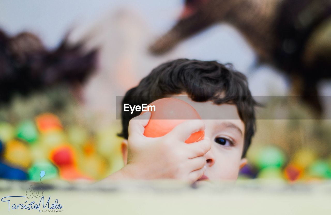 focus on foreground, childhood, toy, day, close-up, real people, headshot, outdoors, one person