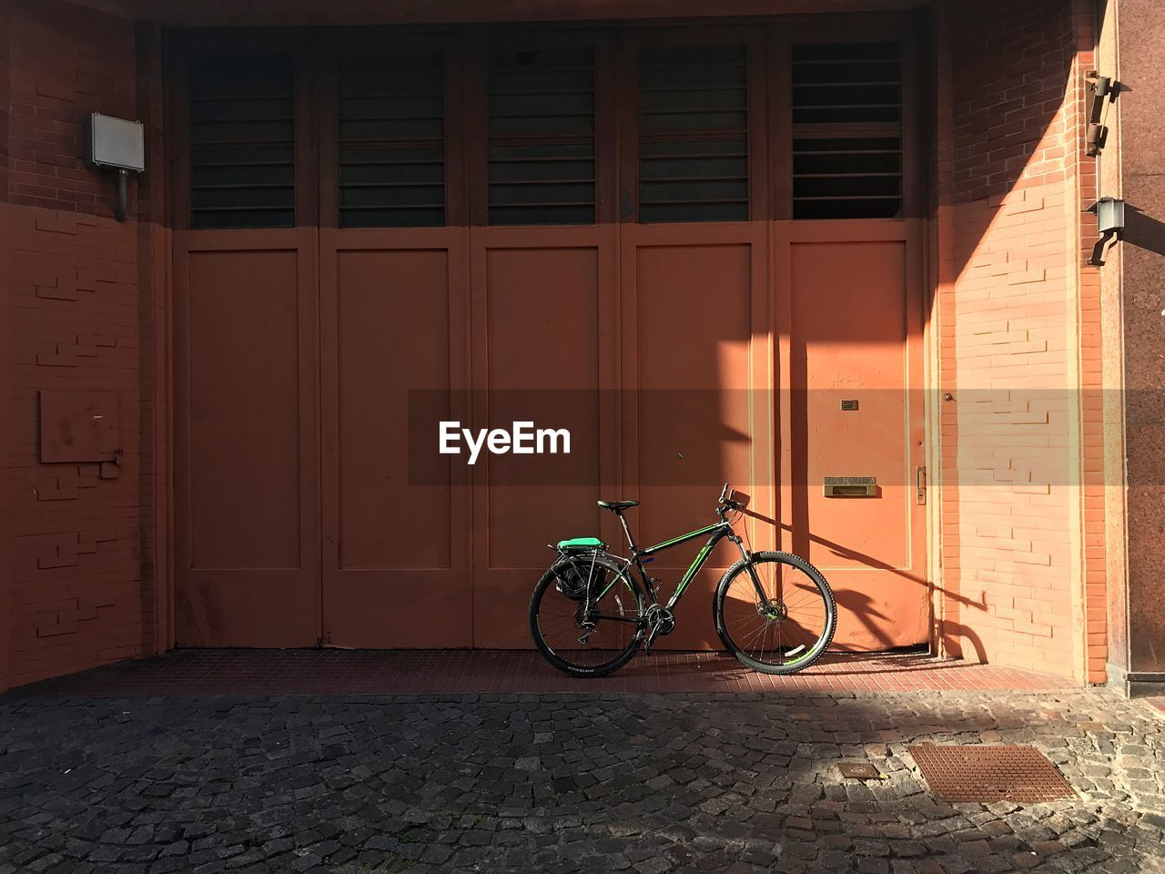 bicycle, built structure, architecture, transportation, land vehicle, mode of transportation, building exterior, stationary, wall - building feature, building, parking, day, city, no people, outdoors, sunlight, entrance, orange color, door, footpath, garage