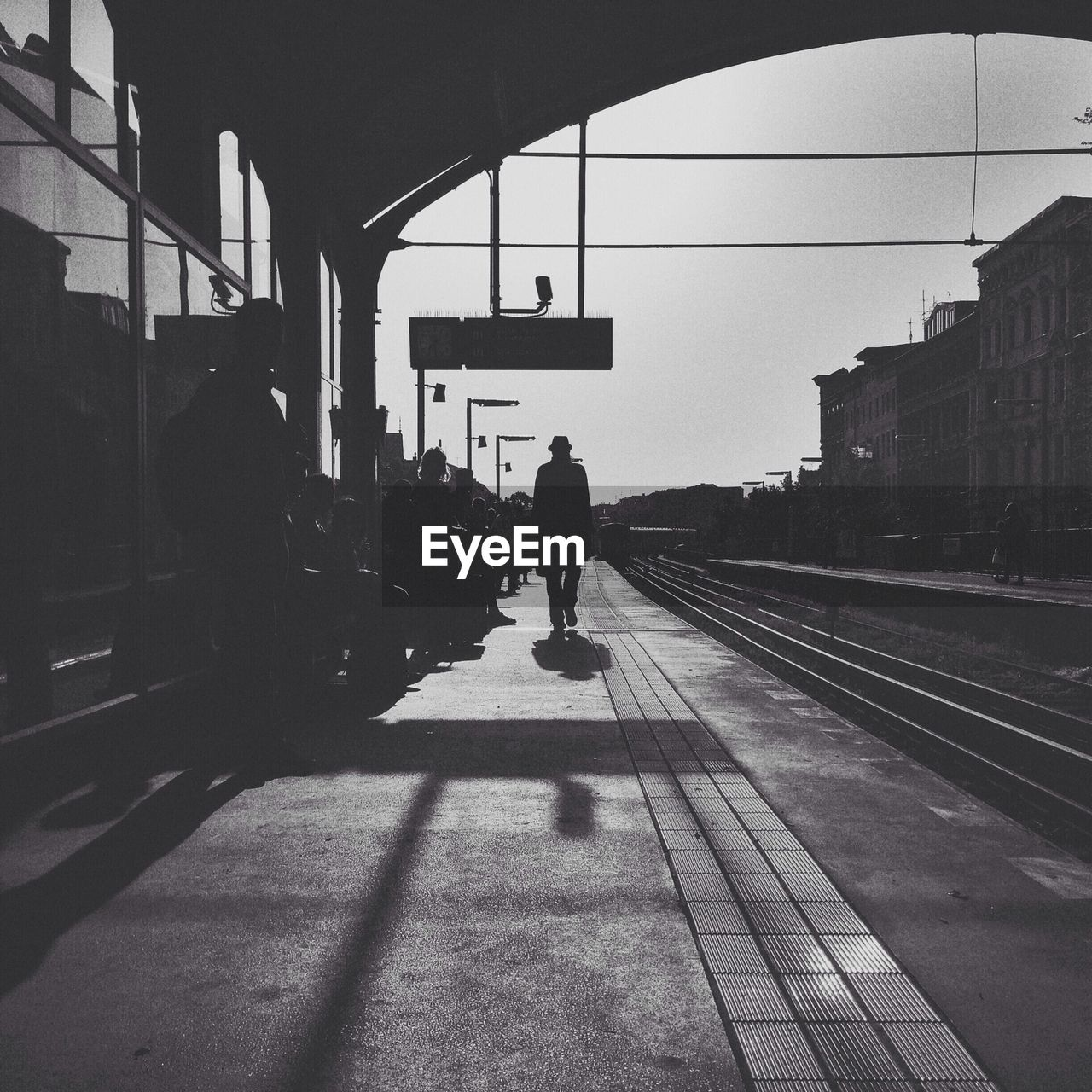 Silhouette people waiting on railroad station platform