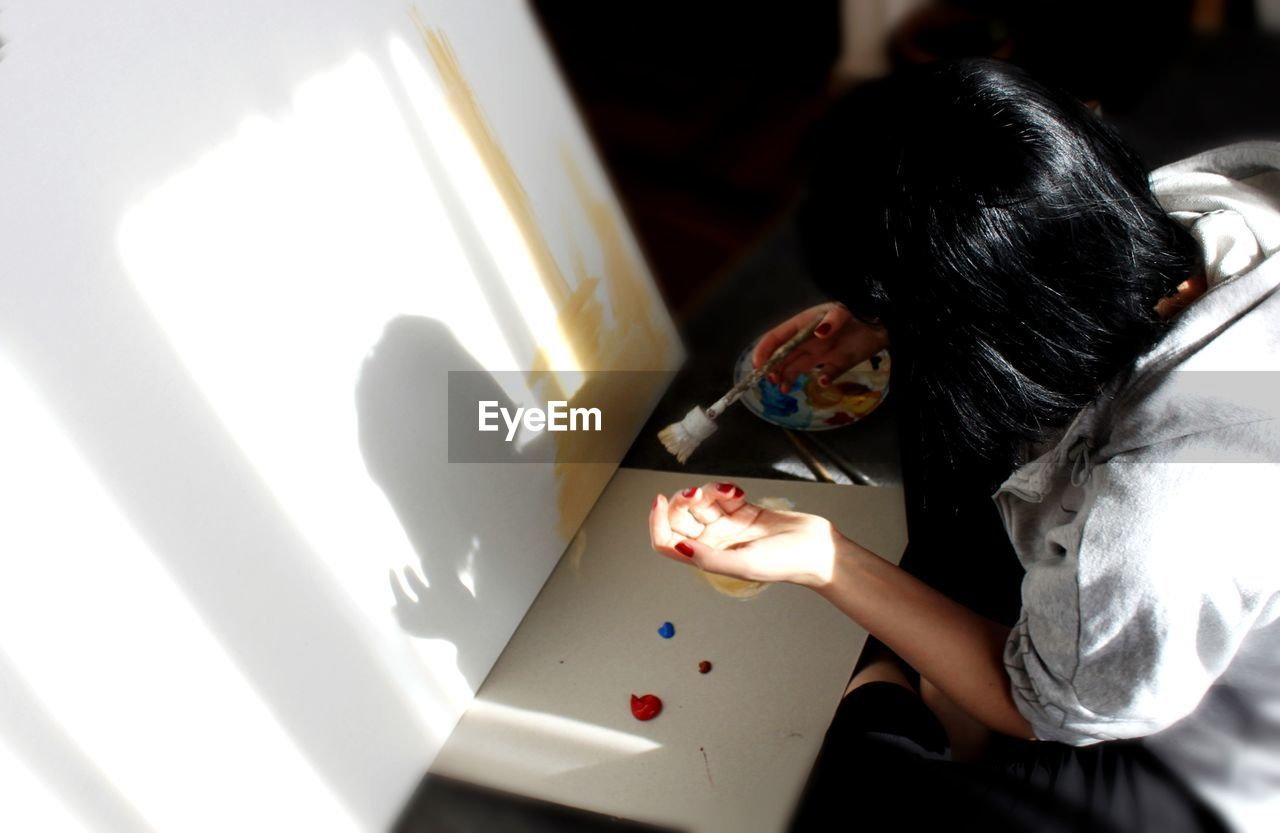 High angle view of woman painting at home