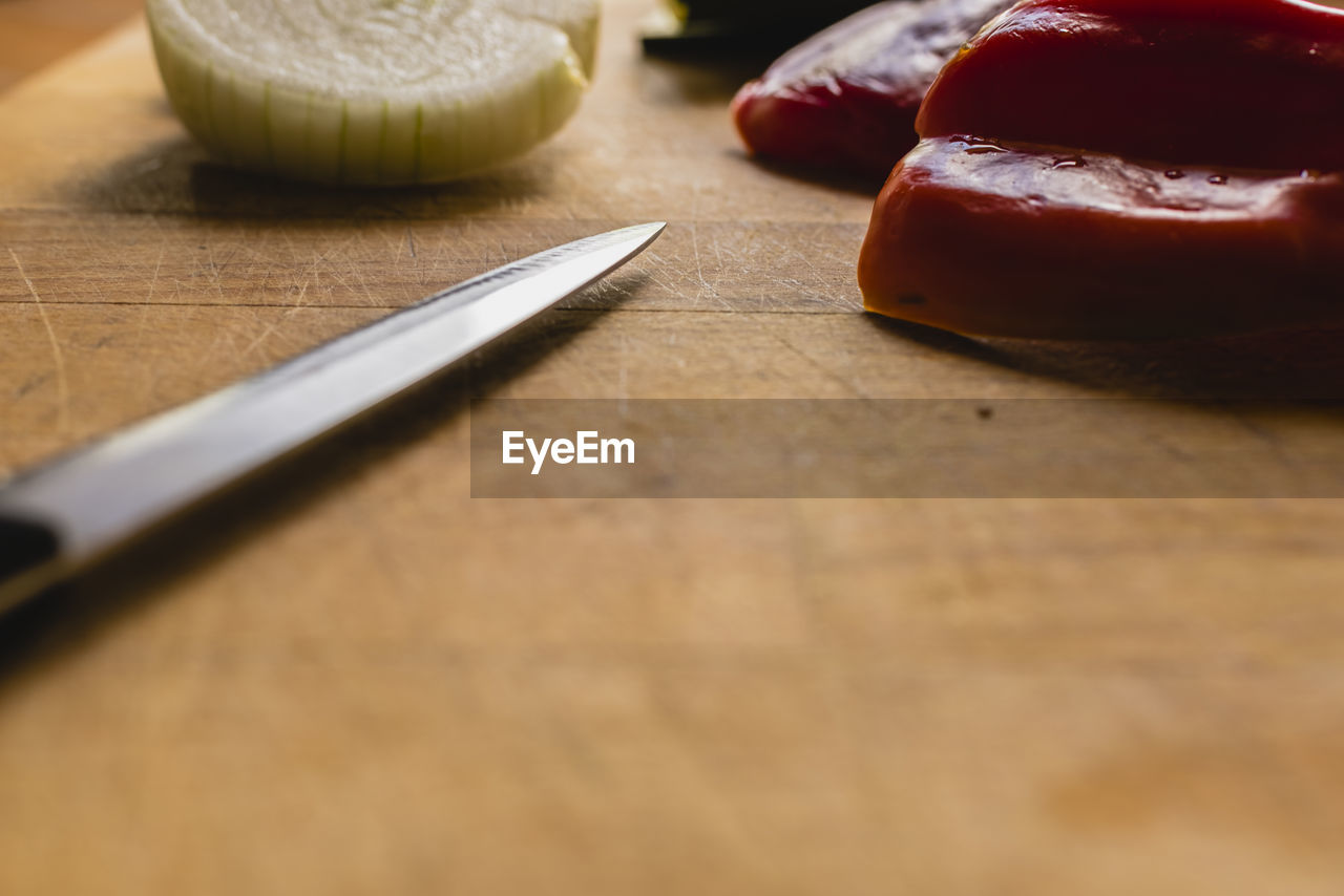 food, food and drink, table, still life, kitchen knife, indoors, freshness, cutting board, selective focus, wood - material, knife, no people, close-up, slice, healthy eating, eating utensil, indulgence, wellbeing, bread, household equipment, temptation, table knife, chopped
