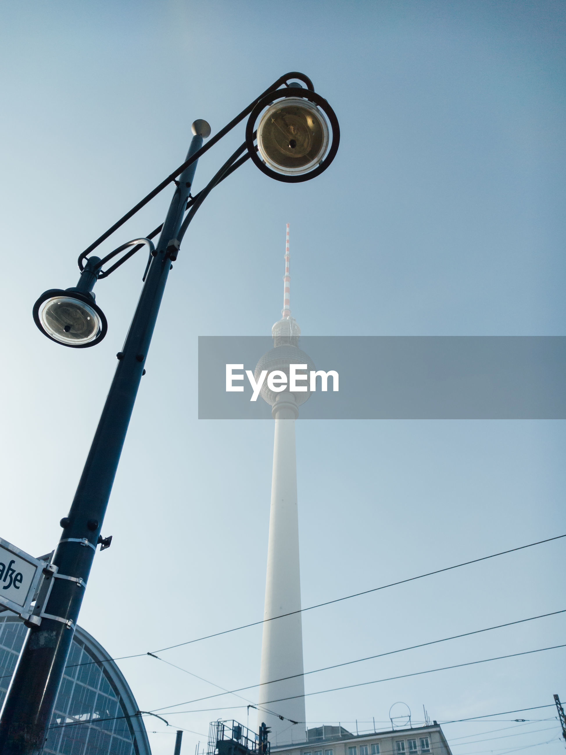 Low angle view of street light and fernsehturm against clear sky