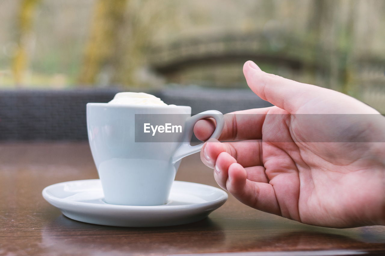 CLOSE-UP OF HAND HOLDING CUP OF COFFEE WITH SPOON