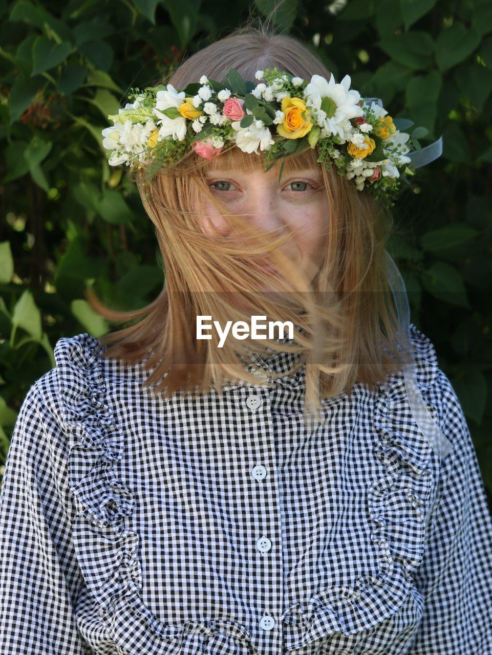 Portrait of woman wearing flowers standing against plants in park