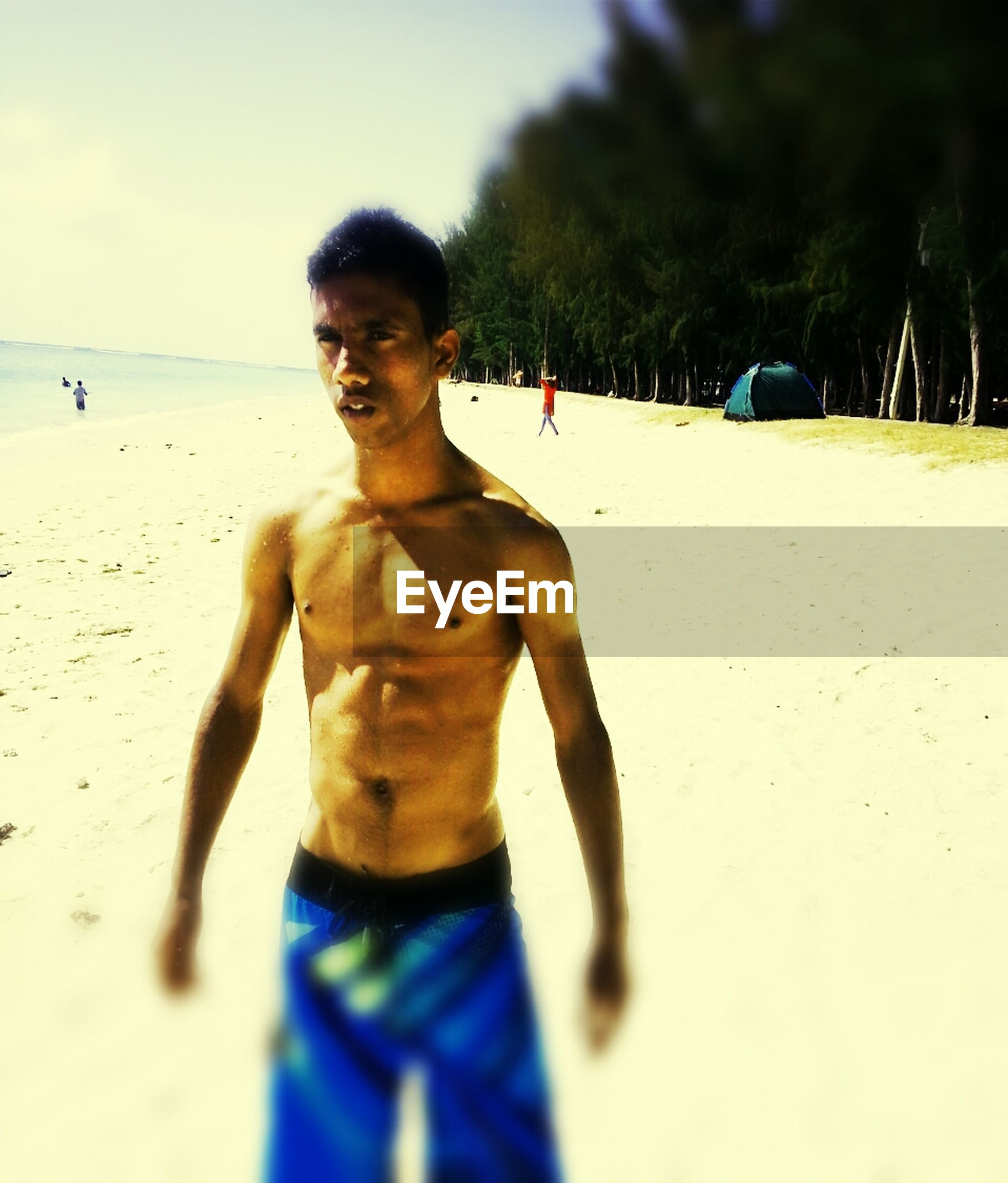 beach, sand, lifestyles, leisure activity, sea, person, shore, young adult, casual clothing, vacations, standing, horizon over water, water, looking at camera, young men, sky, front view, happiness