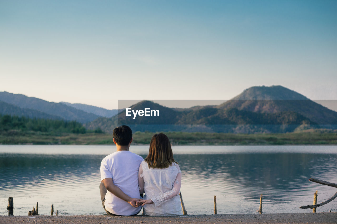 Rear View Of Couple Holding Hands While Sitting By Lake Against Mountains