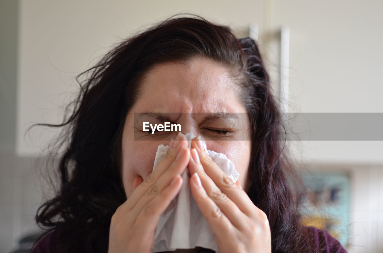 Woman blowing her nose with tissue at home