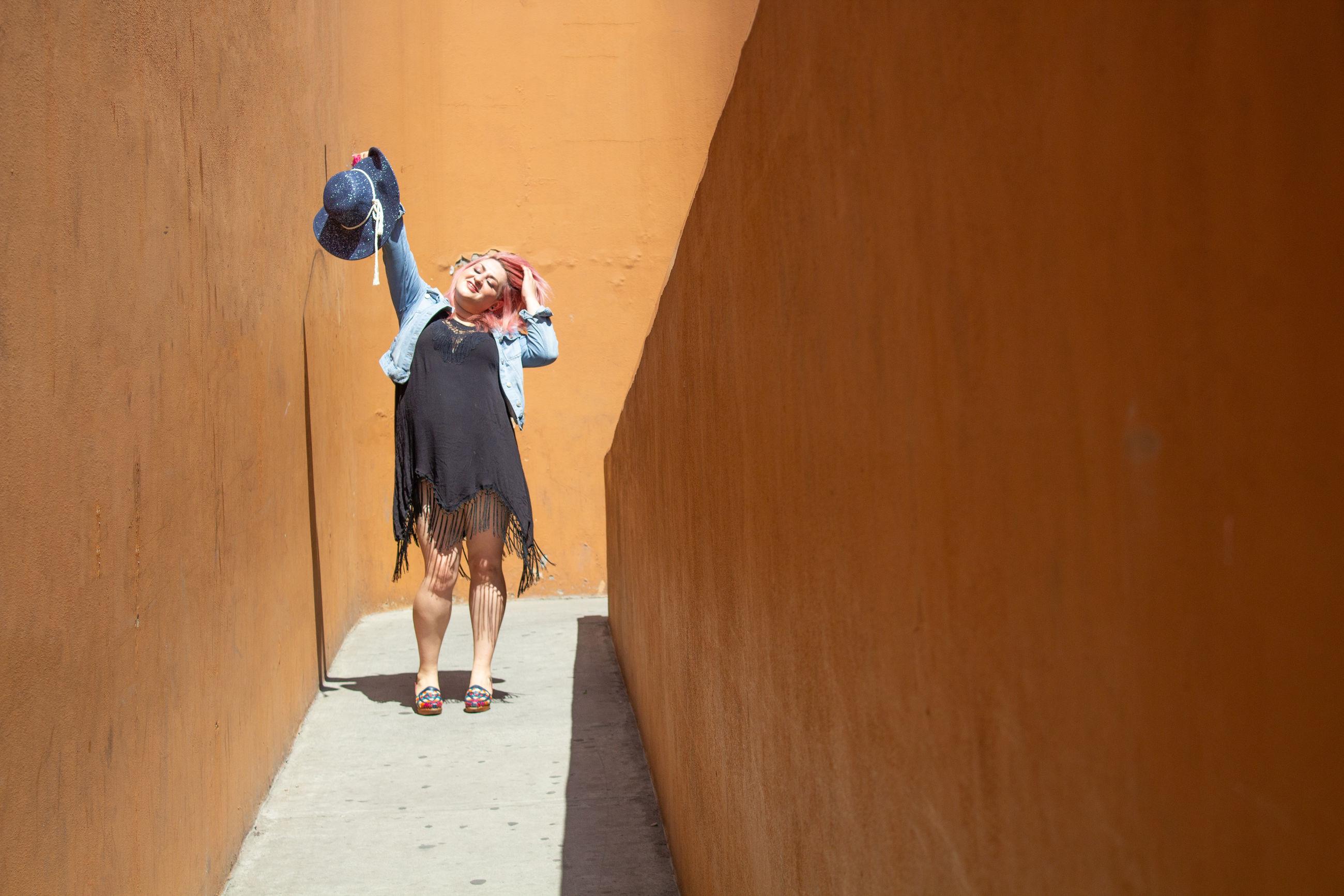 Happy woman walking in orange tunnel moving her hat