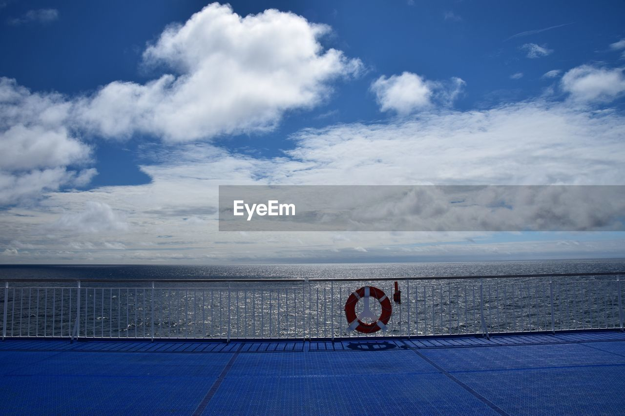 Lifebelt on railing of boat deck at sea against cloudy sky