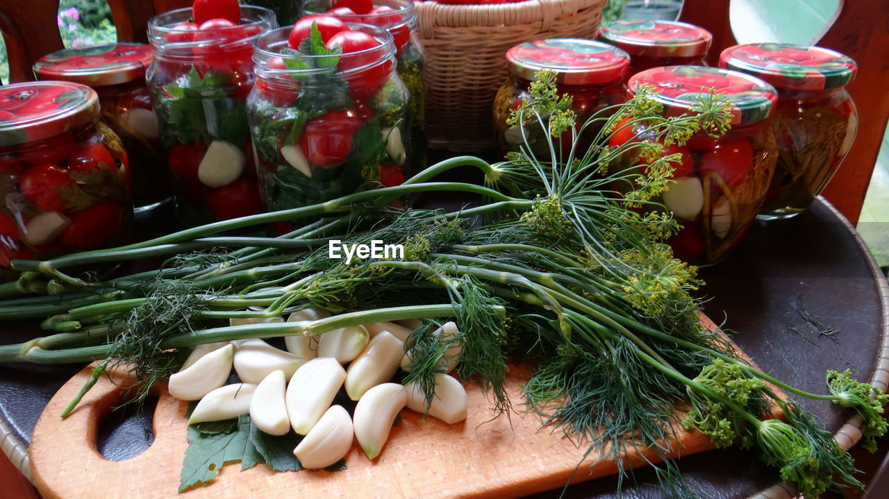 Close-Up Of Garlic And Dill On Cutting Board By Jars At Kitchen Counter