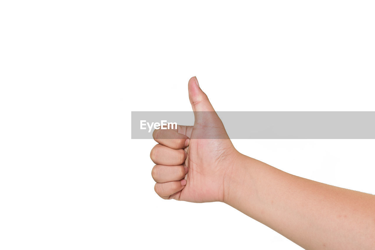 Cropped hand showing thumbs up against white background