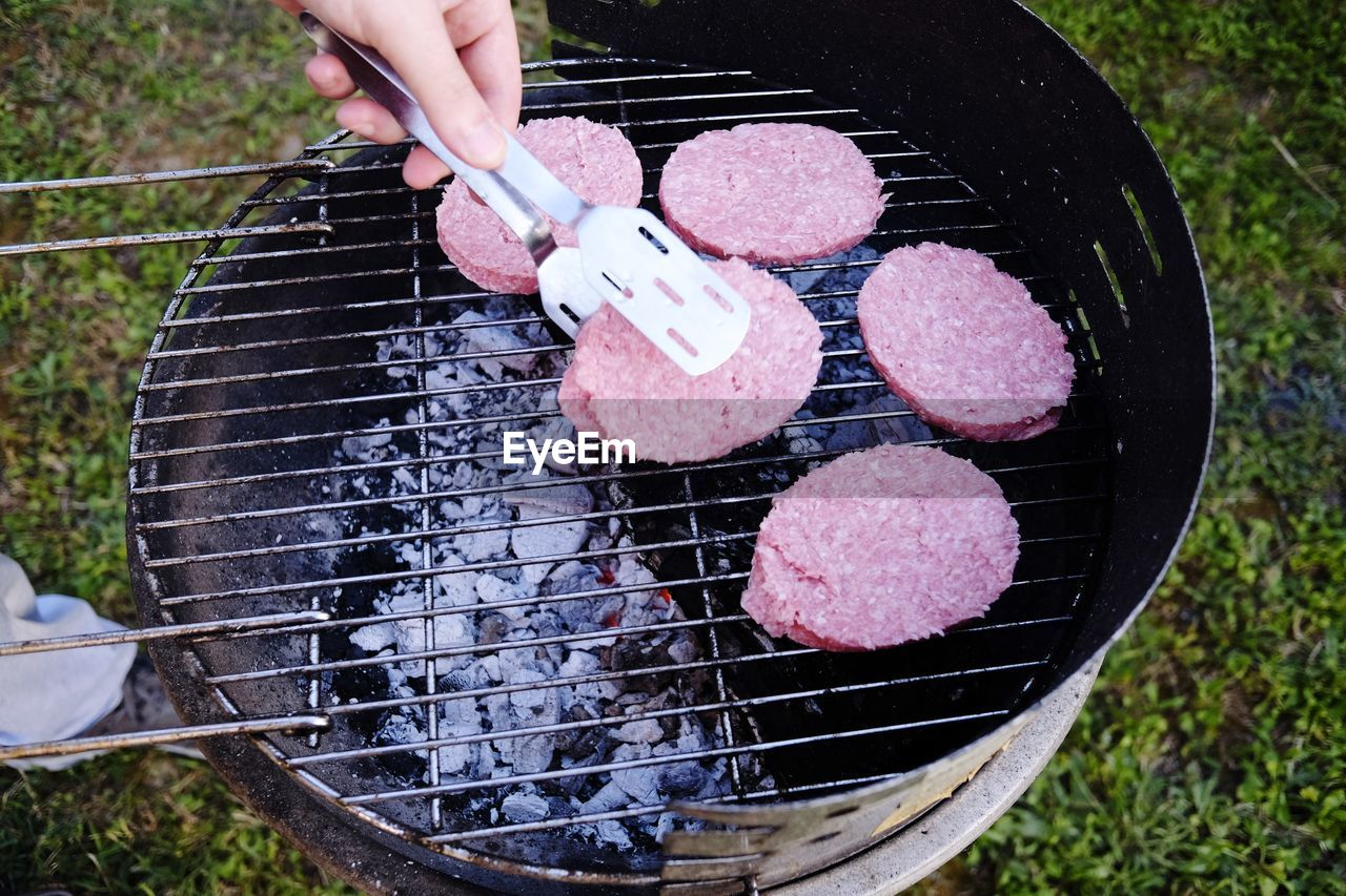 food, human hand, food and drink, barbecue, hand, freshness, preparation, barbecue grill, one person, human body part, meat, preparing food, high angle view, day, grilled, real people, outdoors, heat - temperature, holding, finger, temptation