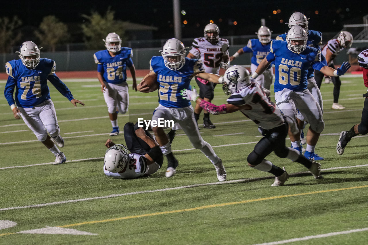 sport, competition, running, group of people, american football - sport, motion, full length, clothing, sports uniform, american football player, competitive sport, helmet, people, playing, sportsman, challenge, athlete, sports team, headwear, american football - ball, teenager, outdoors, effort, adolescence