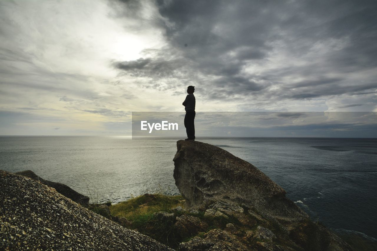 sky, cloud - sky, sea, rock, water, horizon, rock - object, standing, one person, solid, horizon over water, scenics - nature, real people, beauty in nature, full length, nature, tranquility, beach, outdoors, looking at view