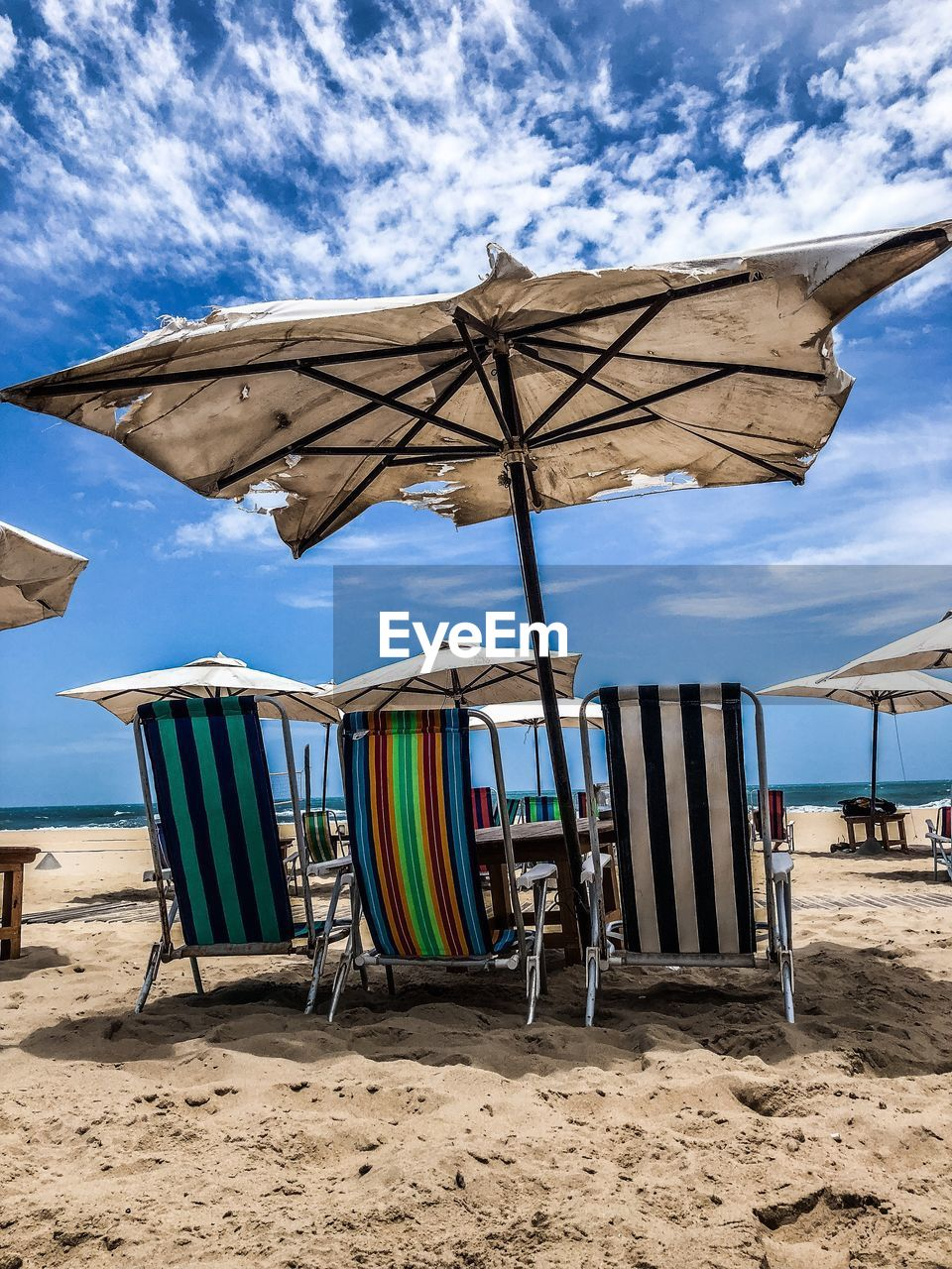 beach, sand, land, sky, chair, parasol, nature, cloud - sky, protection, shade, umbrella, day, absence, water, seat, security, sunshade, sunlight, beauty in nature, no people, outdoors