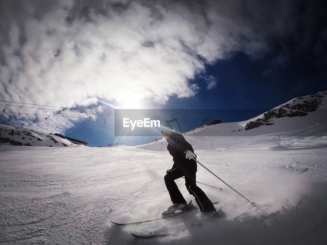 Low Angle View Of Young Woman Skiing On Snow Covered Field Against Cloudy Sky