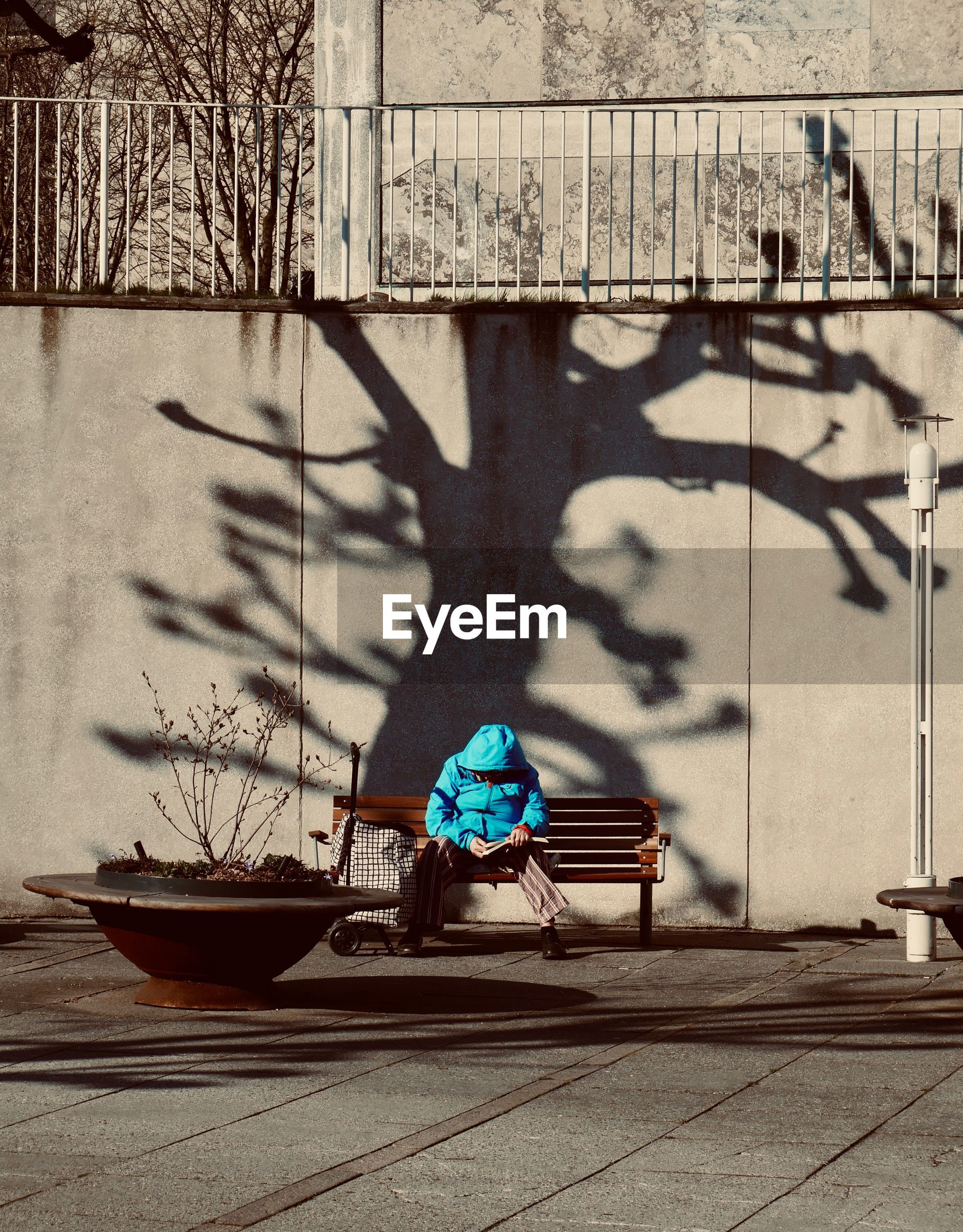 Man reading book while sitting on bench