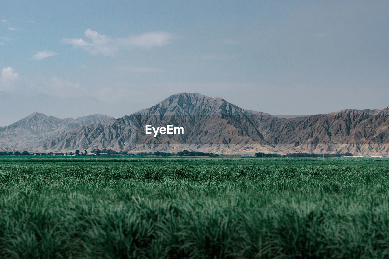 Scenic View Of Land And Mountains Against Sky