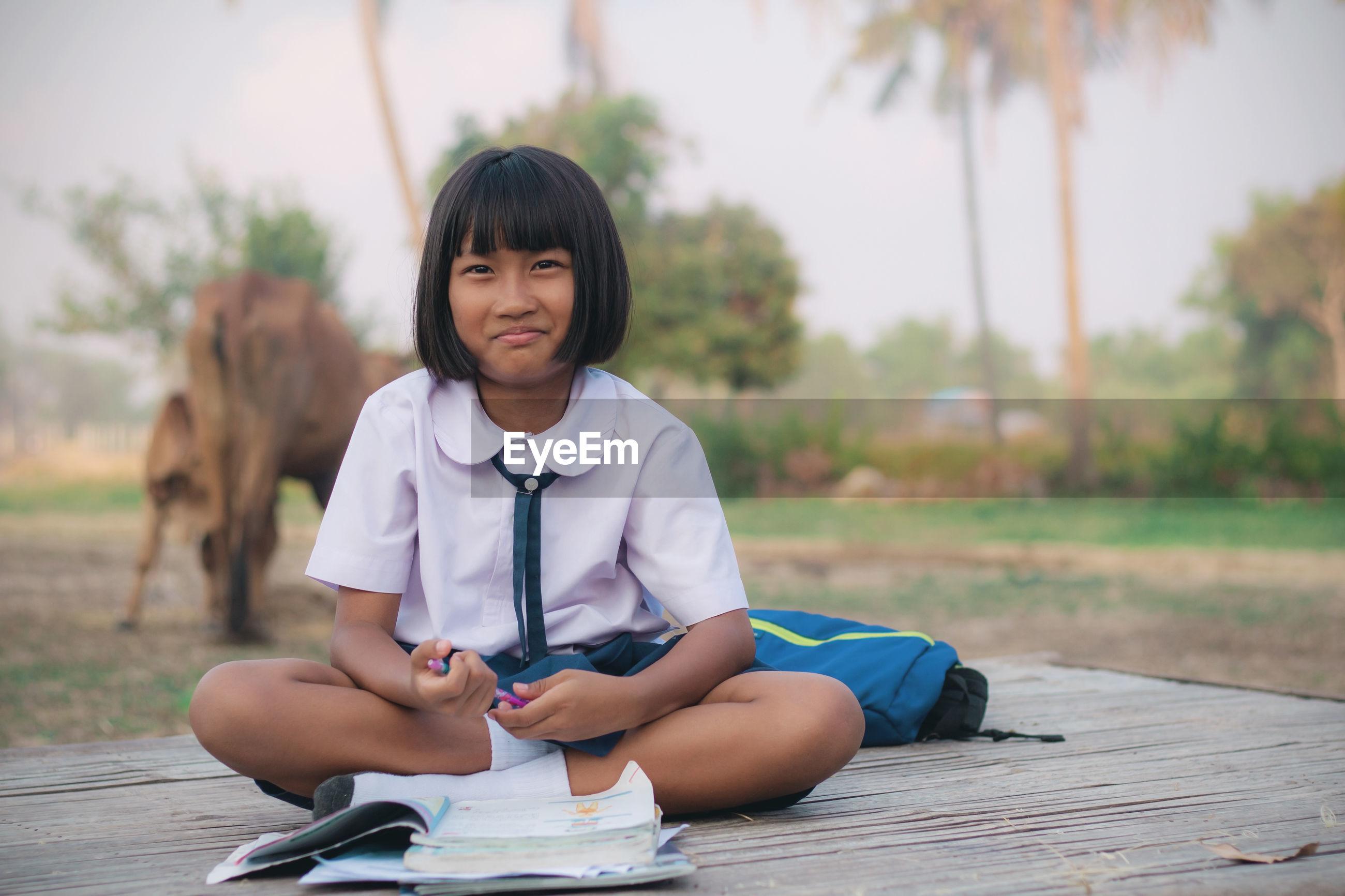 Portrait of smiling schoolgirl studying outdoors
