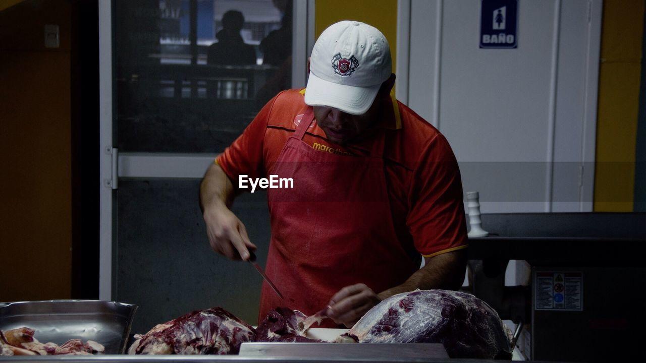 Close-Up Of Butcher Cutting Meat In Butcher Shop