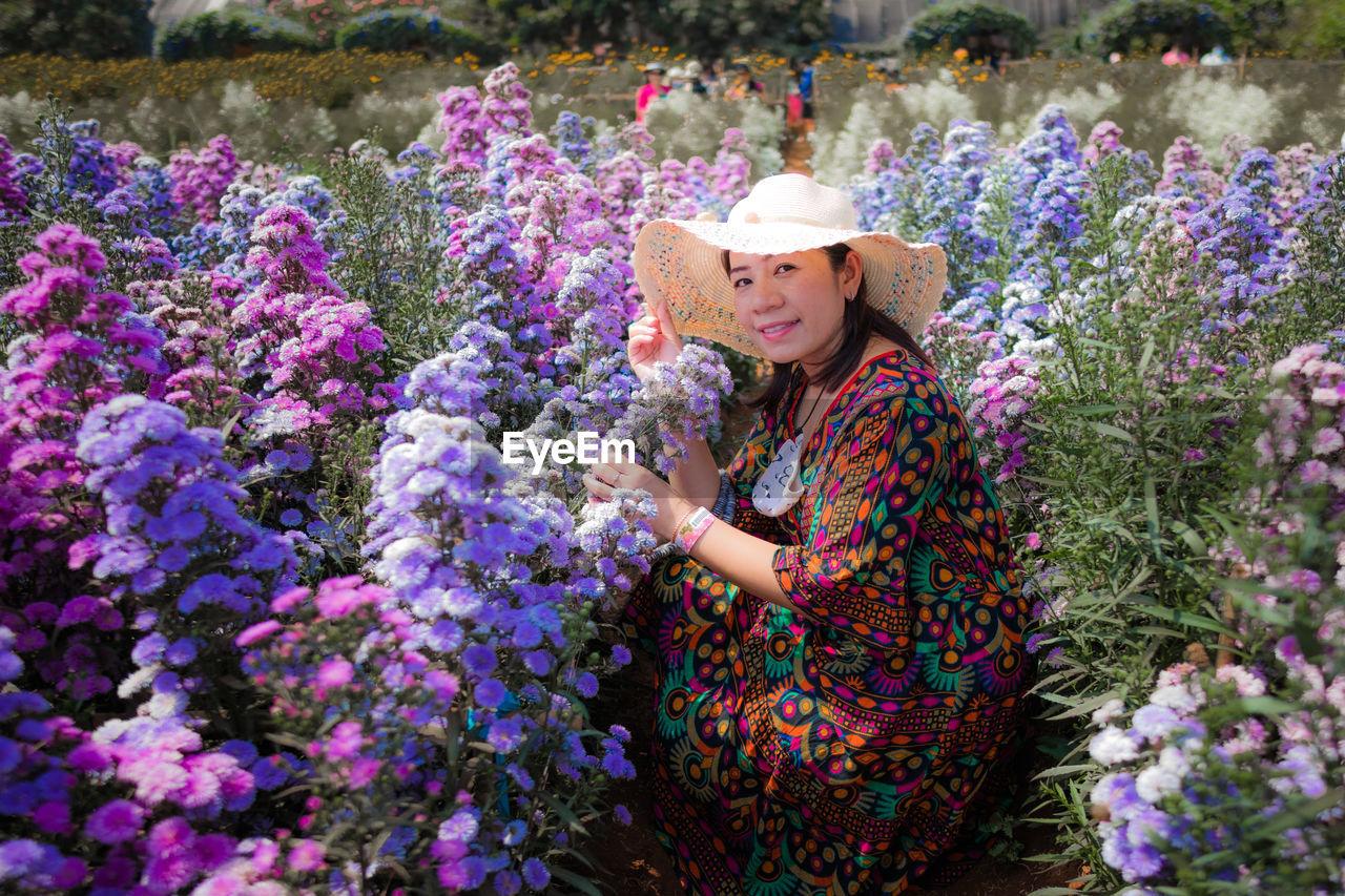 Portrait of woman with purple flowers in garden