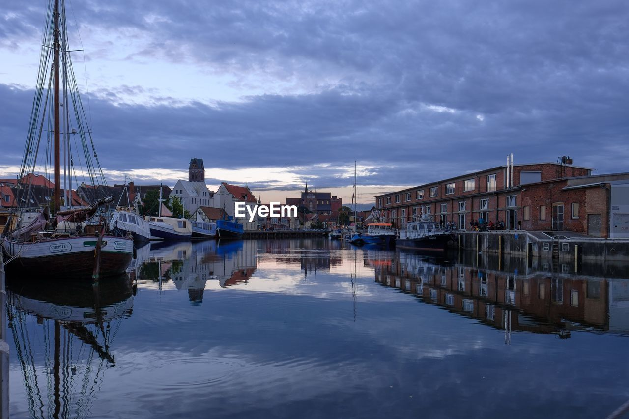 water, cloud - sky, reflection, sky, nautical vessel, transportation, waterfront, building exterior, architecture, moored, mode of transportation, harbor, nature, sailboat, built structure, no people, city, building, pole, outdoors, canal, yacht, marina, wooden post, port