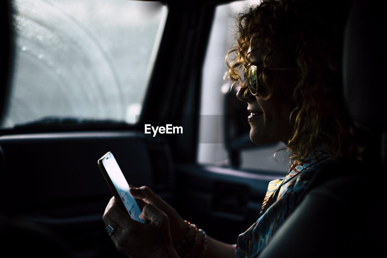 Woman using mobile phone in car