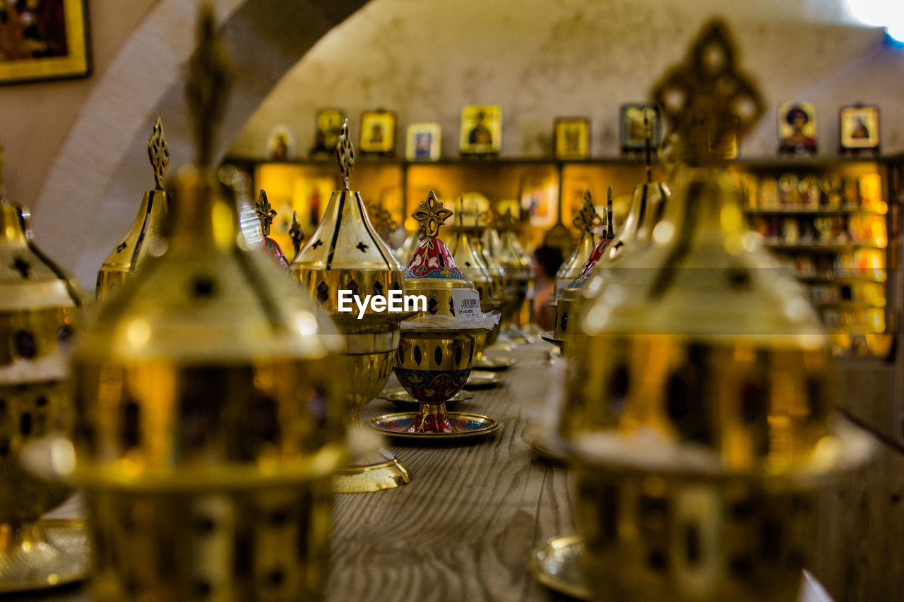 selective focus, arts culture and entertainment, no people, indoors, amusement park, representation, carousel, amusement park ride, architecture, art and craft, creativity, day, carousel horses, close-up, focus on background, in a row, animal representation, business, yellow, wheel