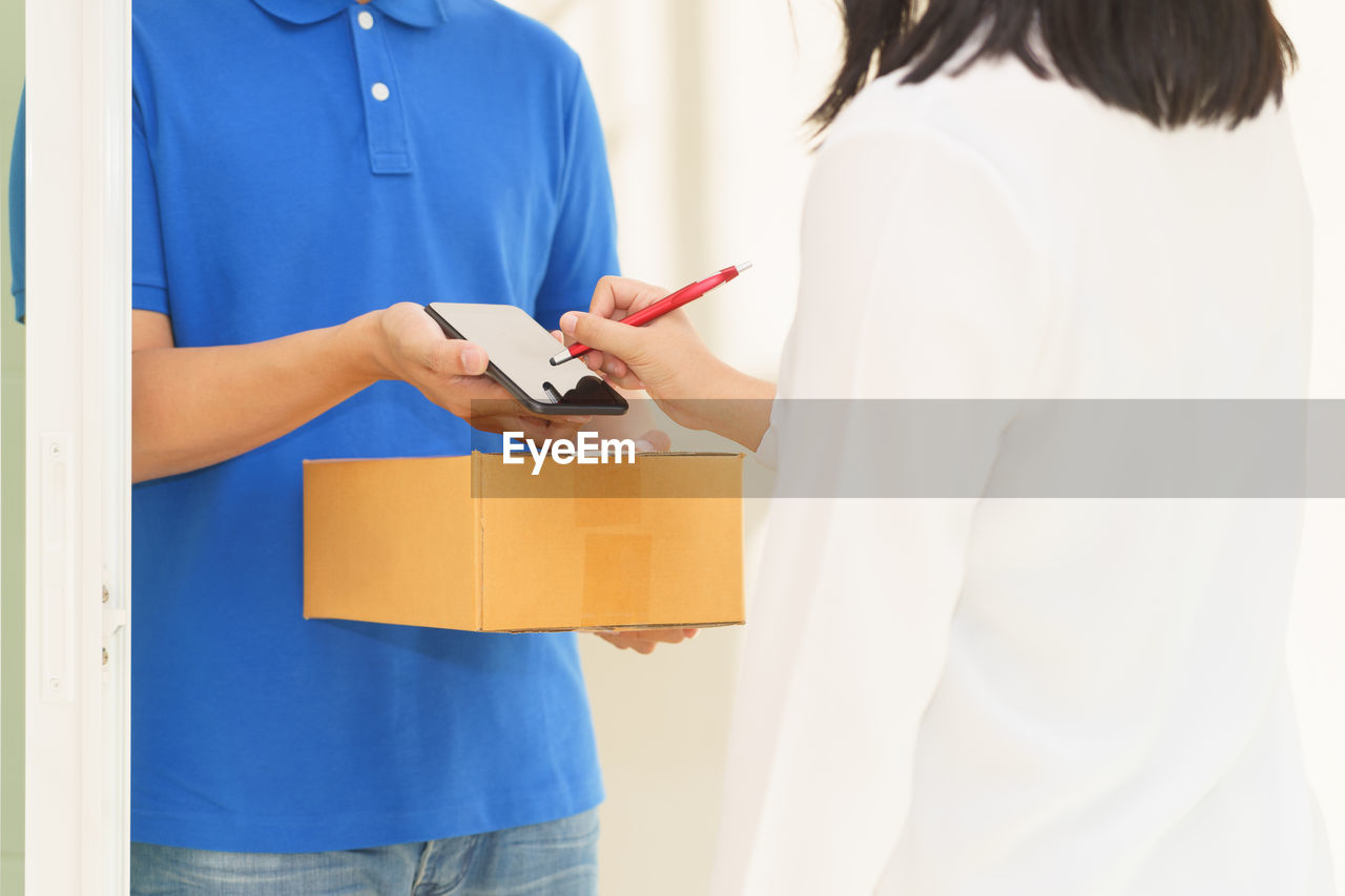 Midsection of woman signing while claiming parcel from delivery person